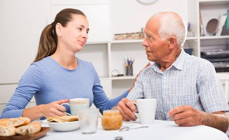 Elderly father and adult daughter talk and drink tea in the kitchen