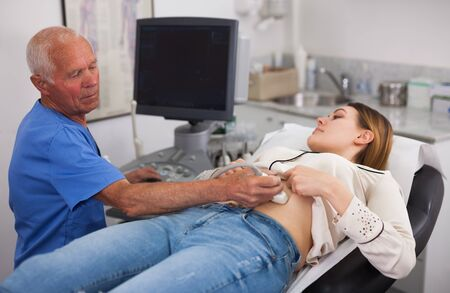 Skilled male doctor diagnosing female patient using modern ultrasound scanner in private clinic