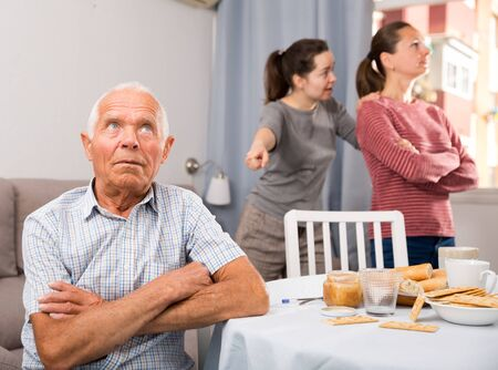 Upset elderly man sitting, young woman with mother havilng conflict on background