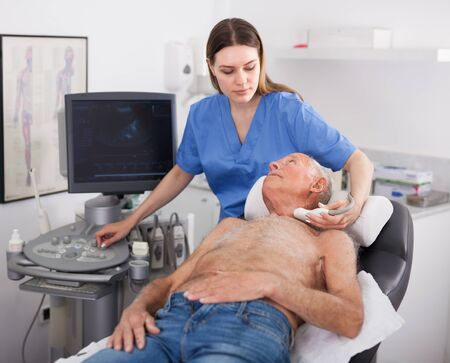 Senior man patient undergoing examination thyroid lying by woman doctor with ultrasonography device