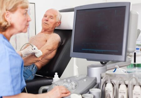 Female doctor using the ultrasound scan examining male patient in a modern hospital