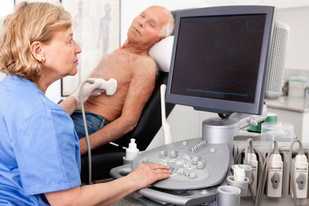 Skilled diligent cheerful smiling woman sonographer using ultrasonography machine checking patient in hospital diagnostic room Zdjęcie Seryjne