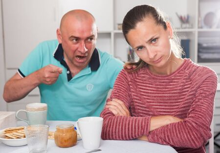 Husband displeased with his wife. Family quarrel in the kitchen