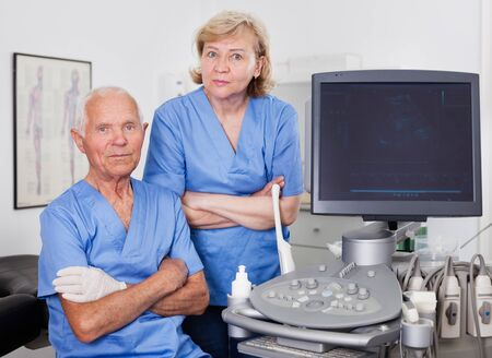 Portrait of qualified male and female doctors near modern ultrasound machine in the medical center Stock Photo