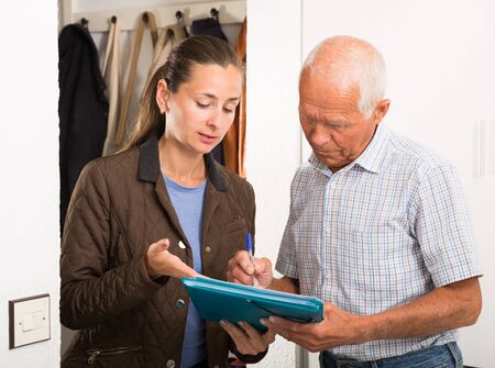 Elderly man signing financial agreement with bank worker at home