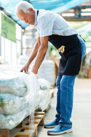 Senior man choosing fertilizers for his farmland in warehouse of garden consumables