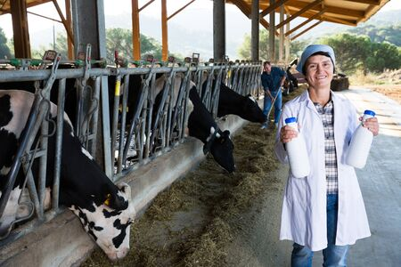 Portrait of woman quality expert who is standing at the cow farm. Archivio Fotografico - 133854561