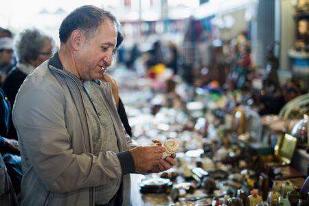 Positive mature man choosing vintage handicrafts at sale on market 写真素材 - 133854563