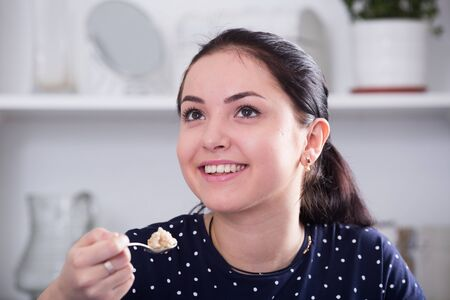 Young smiling girl sitting at table and eating cereal for breakfast Imagens