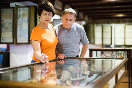 adult man and his wife are visiting museum and standing near exposition under glass indoor.