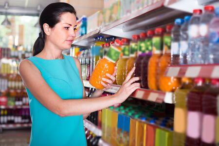 Girl is holding bottle with juice in the shop. Foto de archivo