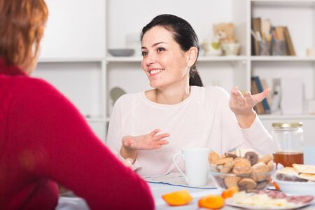 Happy young woman talking with mother at table in home together