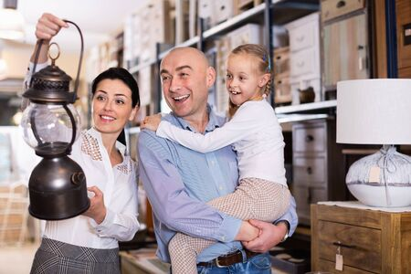 Happy cheerful family is choosing new lamp for home in the furniture store.