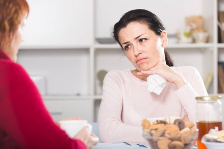 Unhappy female talking with mother at table with food in home