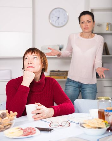Two women having serious quarrel and talking at table in home interior