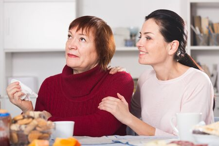 Upset mature woman quarrel with daughter sitting at table in home