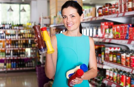 Positive woman choosing different sauces at the modern supermarket Stock Photo