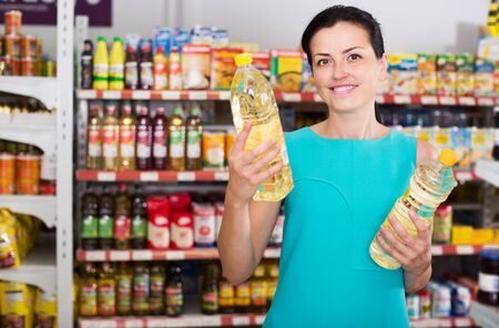 Glad woman choosing different oil in bottle at the supermarket