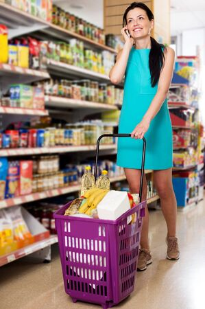 Cheerful woman with cart talking on the phone in the supermarket