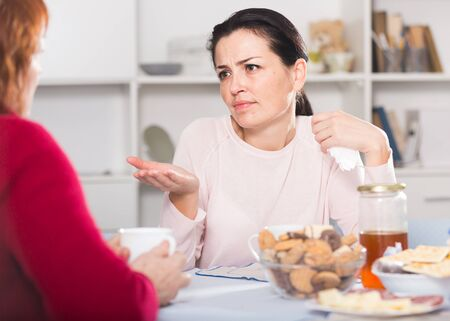Portrait of sad female talking with mother at table with cookies