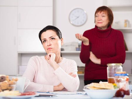 Mature female talking with young sad daughter at table with food