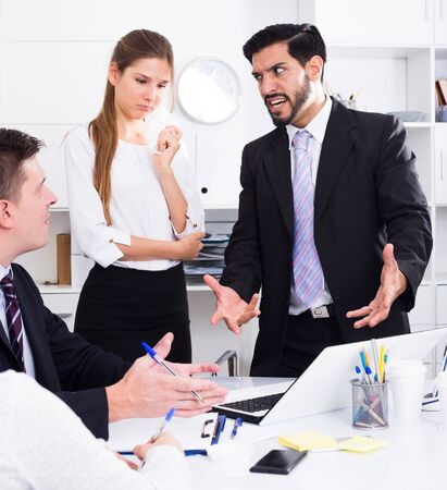 Outraged manager expressing dissatisfaction with teamwork of colleagues at meeting
