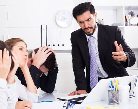 Irritated boss scolding subordinates pointing out shortcomings and misses in work Banco de Imagens