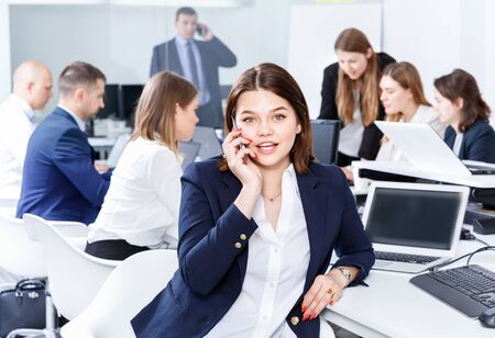 Successful young happy cheerful smiling business woman with phone relaxing at workplace in modern office