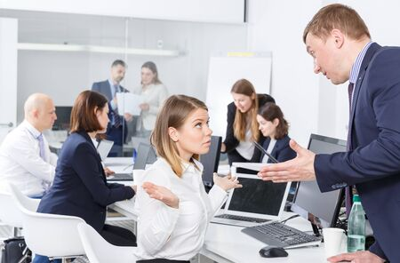 Upset girl sitting at laptop in office while dissatisfied businessman pointing out mistakes in her work Banco de Imagens