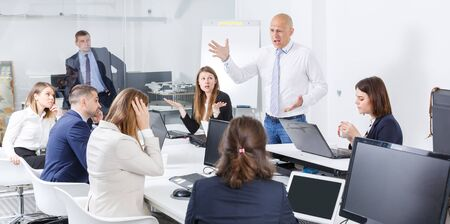 Manager expressing dissatisfaction with teamwork of colleagues at meeting