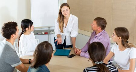 Woman reading out report to colleagues on meeting in office