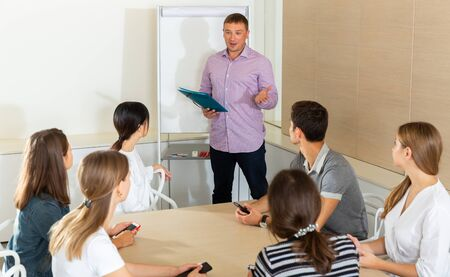 Manager presenting strategy to colleagues in modern office