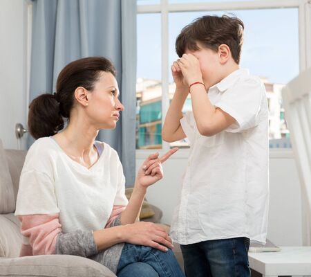 Portrait of strict young woman reprimanding her crying preteen son in home interior Stok Fotoğraf
