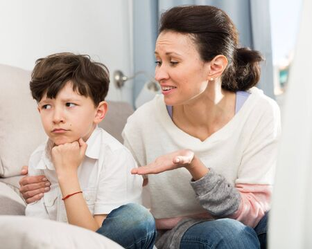 Loving mother consoling sad preteen son after home disagreements