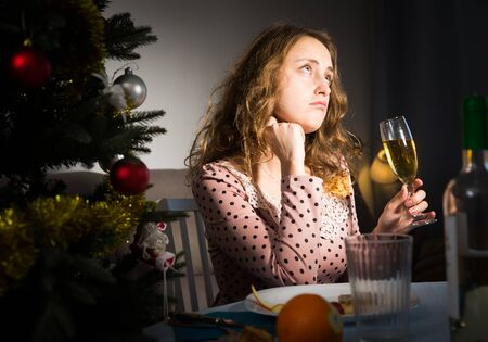 Portrait of frustrated lonely young woman at New Year night at dining table