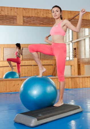 Woman does exercises on fitball in gym with fitness equipment Archivio Fotografico - 133855434