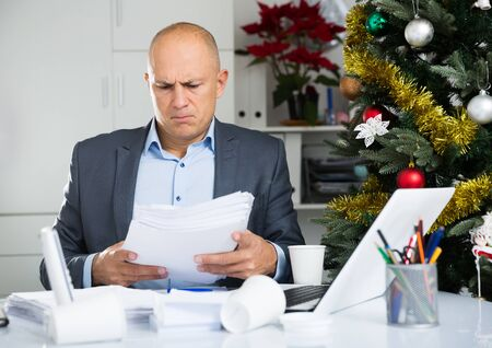 Portrait of worried young man using laptop, working at home at christmastime