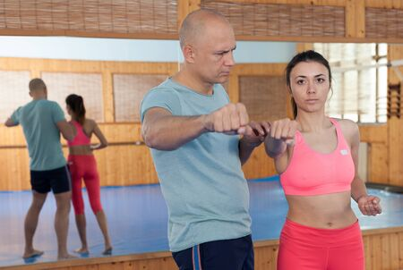 Womens self-defense workout with personal trainer, fighting training in gym Standard-Bild - 133855485