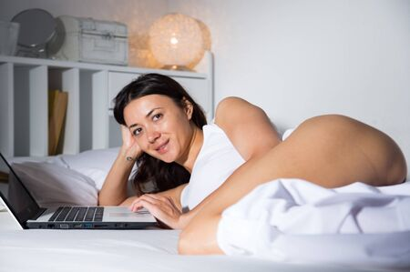 Attractive young woman relaxing  with notebook in bedroom at home interior