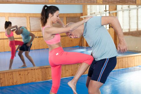 Ordinary female is fighting with trainer on the self-defense course for woman in sport club Banque d'images