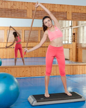 Woman doing exercise with gymnastic stick in fitness club