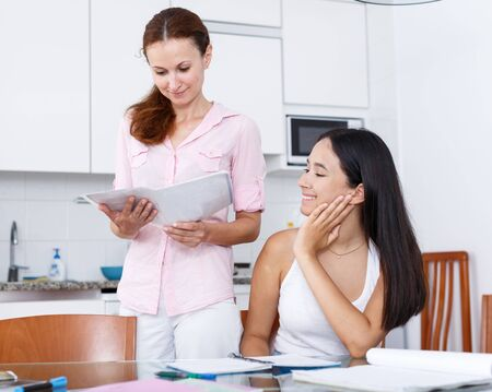 Mother rejoicing that her daughter is doing well in school in kitchen interior Stock Photo