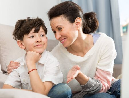 Preteen boy upset about something and his mother gently soothing him at home. Concept of difficult age Archivio Fotografico - 133855527