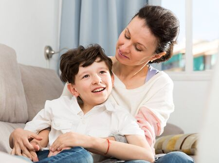 Happy family of young mother and preteen son spending time together at home