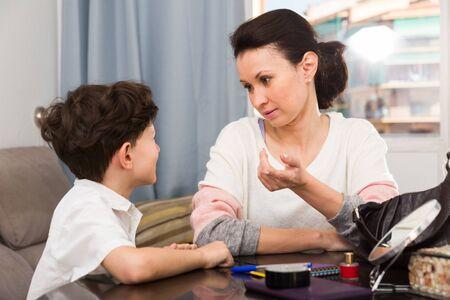 Mujer estricta que tiene una conversación seria con su hijo preadolescente en casa