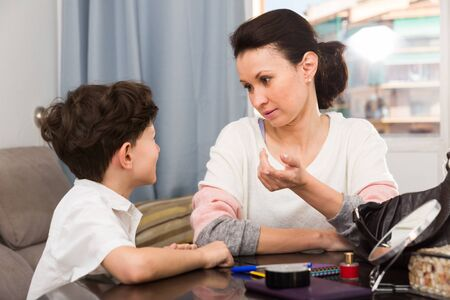 Strict woman having serious conversation with her preteen son at home