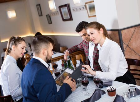 Ñheerful positive smiling friends choosing dishes out of menu card in restaurant