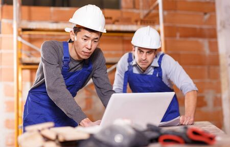 Asian and Hispanic workers looking at laptop with blueprints of building