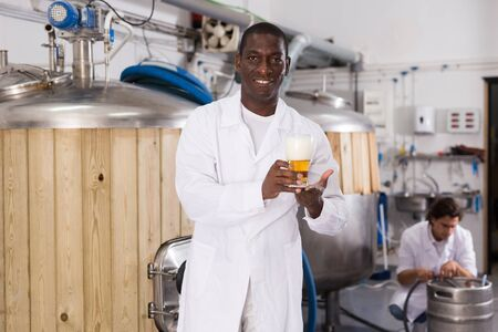 African american man brewer is standing with glass of beer in brew-house