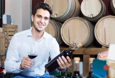 portrait of smiling man holding bottle and glass of wine in alcohol section with woods